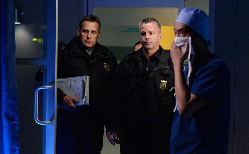 Mit einem Haftbefehl in der Hand suchen Sergeant Cole (Billy Lockwood, M.) und sein Kollege (l.) einen Arzt des Teams. Dr. Topher Zia (Ken Leung) erklärt, dass der besagte Arzt gerade im OP steht. – Bild: MG RTL D / Sony Television Inc.