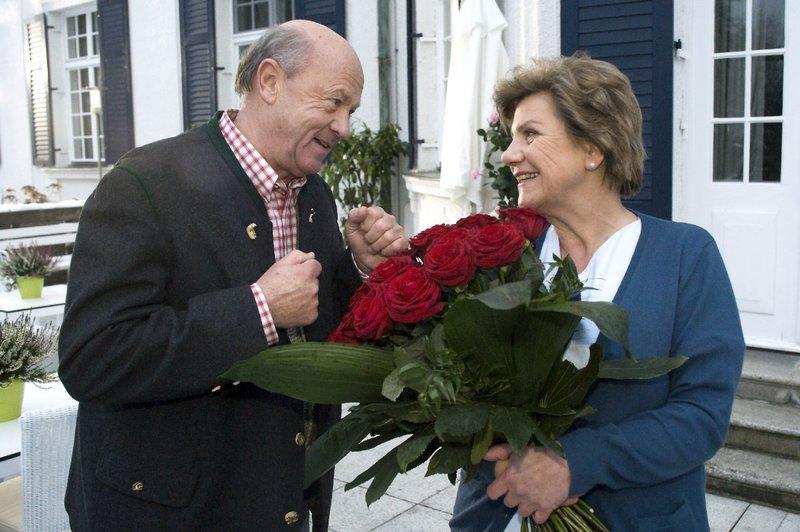 Alois Hofer (Hans Stadlbauer) ist neugierig, wer Oberschwester Ursula Reisinger (Marianne Rappenglück) den großen Strauß Rosen geschenkt hat. – Bild: ORF 2