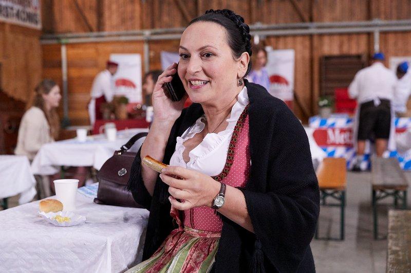Marianne Grasegger (Ursula Maria Burkhart) genießt das Essen auf dem Rosenheimer Brat-wurstwettbewerb. – Bild: ZDF und Bojan Ritan.