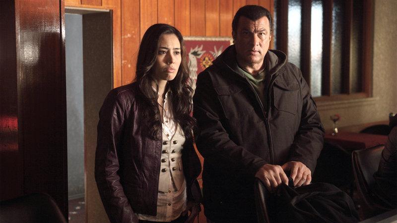 Daniels (Steven Seagal) spürt, dass hinter dem Entführungsfall das organisierte Verbrechen steckt, und bringt sich und das Entführungsopfer Tia (Marliah Mah) in Sicherheit. – Bild: RTL II