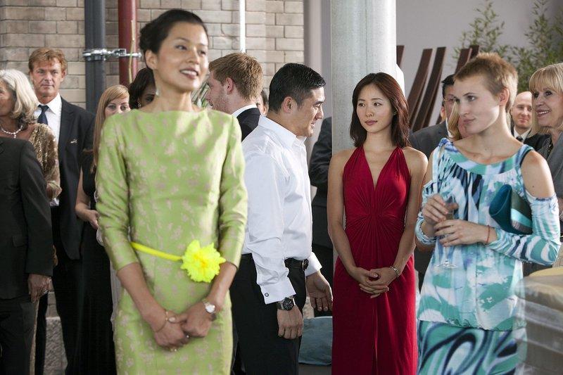 Ling (Jiang Yiyan, rotes Kleid) trifft auf den Geschäftsmann Yu Guanhao (Wu Da Wei, weißes Hemd). – Bild: rbb/rbb/Reverse Angle Production GmbH