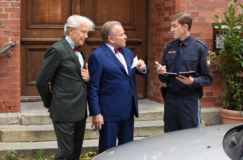 Polizist Meier (Lars Weström, r.) überreicht Wöller (Fritz Wepper, M.) den Strafzettel, den eigentlich sein Halbbruder Friedhelm Breitner (Bernd Herzsprung, l.) kassiert hat. – Bild: ARD/Barbara Bauriedl