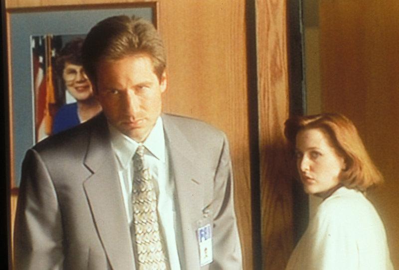 Mulder (David Duchovny, l.) und Scully (Gillian Anderson, r.) verdächtigen ihren Chef, von einer Konspiration zwischen der Regierung und der pharmazeutischen Firma gewusst zu haben, die 18 Menschen das Leben gekostet hat. – Bild: ProSieben MAXX