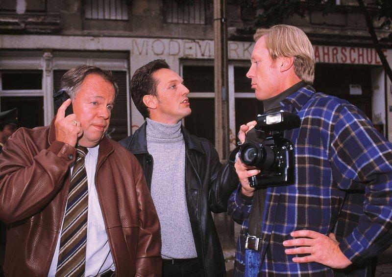 Der Fotograf (Jo Neander, re.), der am Tatort aufgetaucht ist, nervt die Kommissare Kehler (Wolfgang Bathke, li.) und Bongartz (Max Gertsch). Er behindert sie bei ihrer Arbeit. – Bild: RTLplus