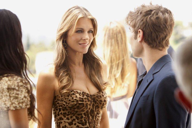 Nate (Chace Crawford, r.) trifft auf einer Filmparty eine geheimnisvolle Frau (Elizabeth Hurley, l.) und gibt vor jemand anderer zu sein, als er ist, um sie zu beeindrucken. Doch sie hat ihn längst durchschaut ... – Bild: Warner Bros. Television Lizenzbild frei
