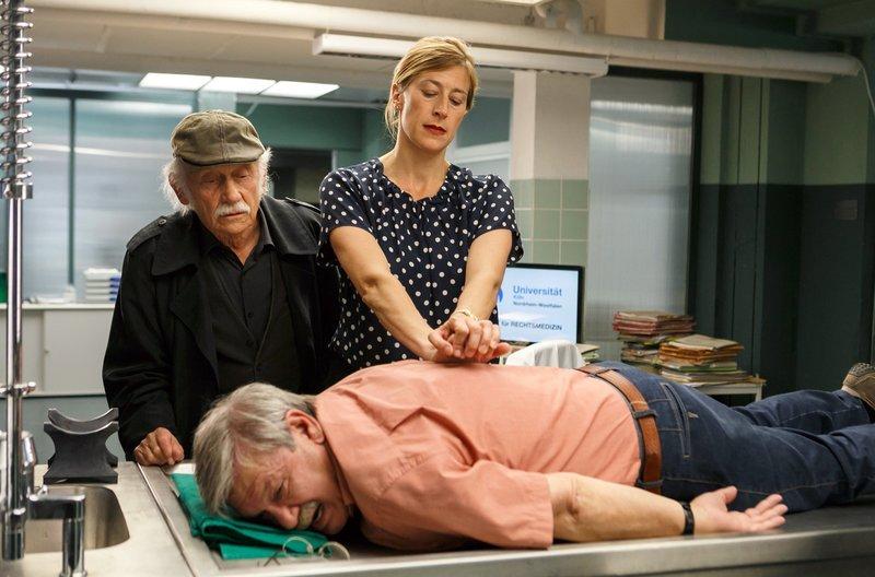 Günter Hoffmann (Wolfgang Winkler, vorne) hat Rücken und lässt sich im Beisein von Edwin Bremer (Tilo Prückner, l.) von Dr. Rosalind Schmidt (Helene Grass, r.) behandeln. – Bild: ARD/Kai Schulz