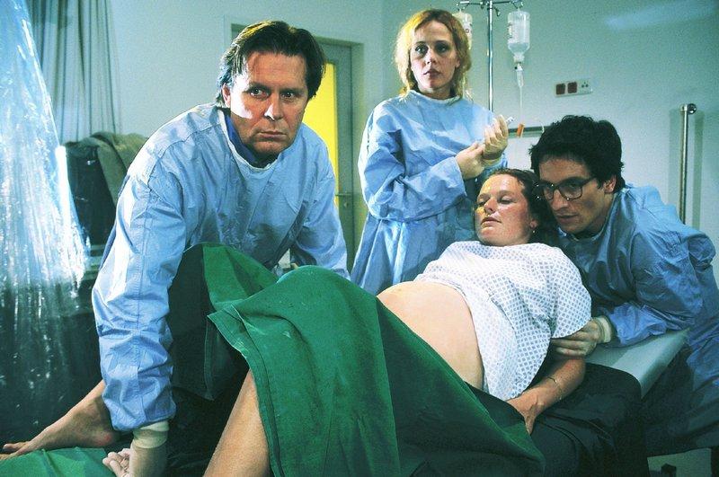 Dr. Stefan Frank (Sigmar Solbach, l.), Schwester Sonja (Patricia Lueger) und Dr. Tim Eckert (Oliver Mommsen) helfen der hochschwangeren Ilona (Gabi Herz) bei ihrer schwierigen Geburt ... – Bild: RTL Passion