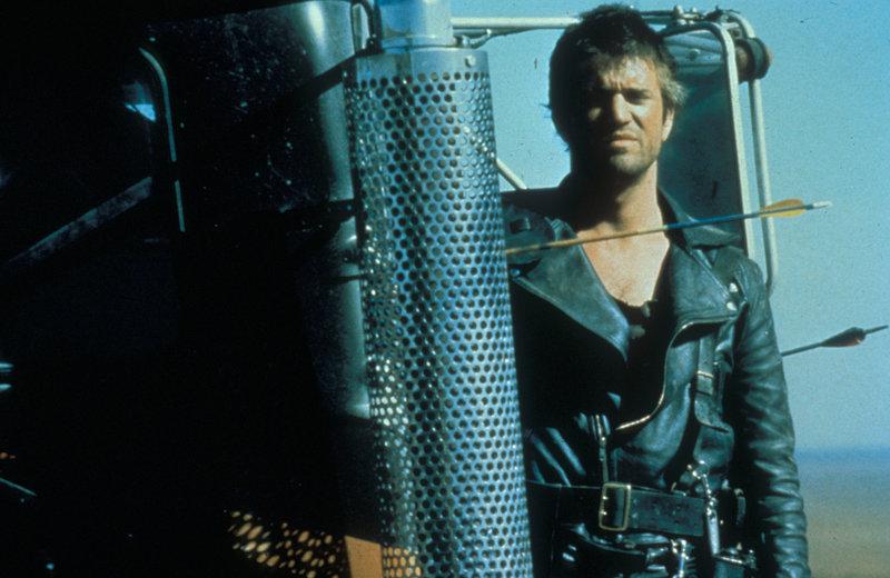 """Die nomadisierende Motorrad-Gang unter der Führung des sadistischen Toecutter liefert sich einen erbitterten Krieg mit einer Polizei-Truppe, die mit hochfrisierten Spezialfahrzeugen ausgerüstet ist. Einer der härtesten dieser Cops ist """"Mad Max"""" (Mel Gibson) ... – Bild: Warner Bros. Lizenzbild frei"""