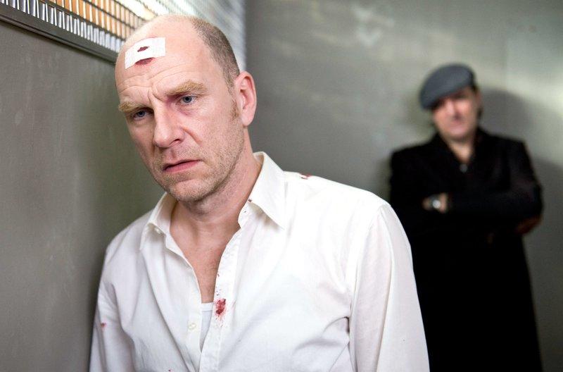Frank Brenner (Götz Schubert, im Hintergrund Andreas Hoppe als Mario Kopper) ist im Gefängnis ausgerastet und hat sich selbst verletzt. Über seine Gründe schweigt er sich genauso aus wie über die Frage, ob er das Auto seiner Freundin manipulierte. – Bild: ORF 2