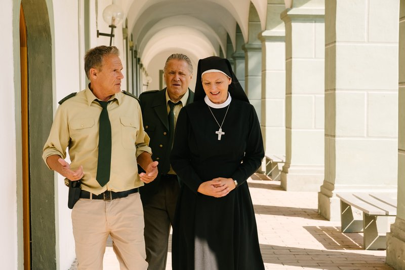 Hubert (Christian Tramitz, l.) und Girwidz (Michael Brandner, m.) befragen Oberin Renate (Michaela Steiger) zu Schwester Lara. – Bild: TMG / Emanuel A. Klempa