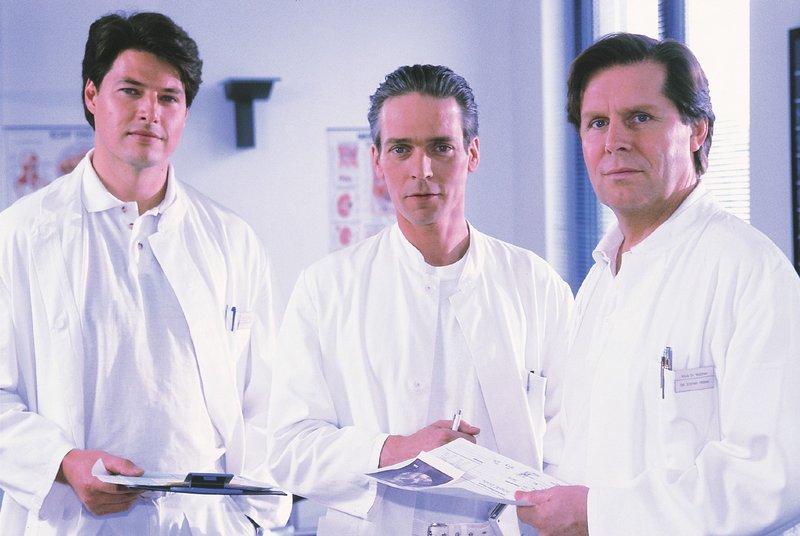 Dr. Stefan Frank (Sigmar Solbach, r.) und Dr. Thomas Reinhardt (Christopher Barker, l.) sind gegen Dr. Jan Winters (Jacques Breuer) Vorschlag, Nadine ein Spenderherz zu transplantieren. – Bild: RTLplus