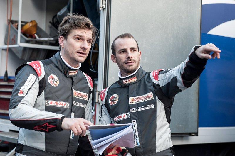 Rennfahrer Max Griebel (Matthi Faust, l.) und sein Co-Pilot Riccardo (Maximilian Allgeier, r.) besprechen die vor ihnen liegende Rennstrecke. – Bild: SRF 1