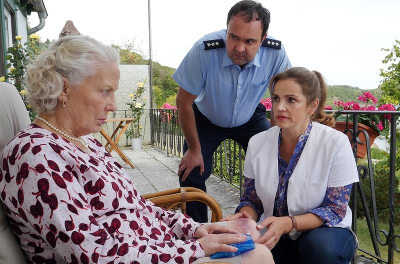 Frau Böhls (Marie Anne Fliegel) Sohn Volker (Tom Keune) und Versorgungsassistentin Vera (Rebecca Immanuel) fragen sich, woher die Verletzung am Knie stammt. – Bild: ARD Degeto/Hans-Joachim Pfeiffer