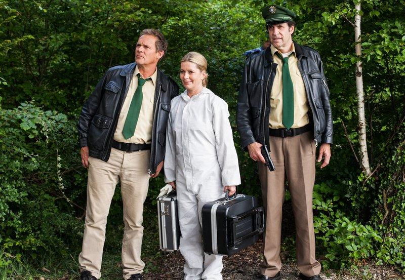 Dr. Anja Licht (Karin Thaler, Mitte) trifft am Tatort ein und erklärt Hubert (Christian Tramitz, links) und Staller (Helmfried von Lüttichau), dass es sich nicht um ein Krokodil, sondern um einen Kaiman handelt. – Bild: ARD/BR/TMG/Chris Hirschhäuser
