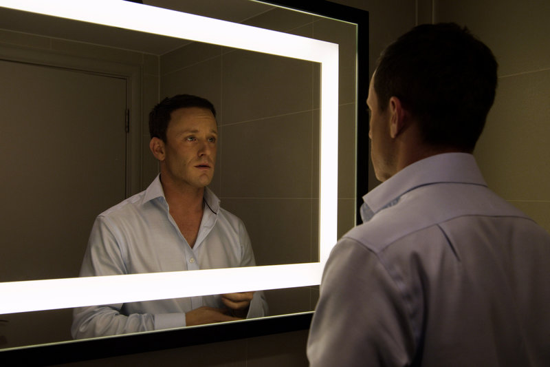 Lance Armstrong (Ben Foster) übt vor einer Pressekonferenz vor dem Spiegel, um Fragen nach möglichem Blutdoping überzeugend abweisen zu können. – Bild: ZDF und Studiocanal GmbH