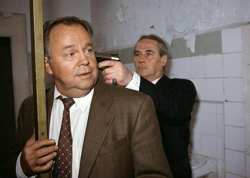 Kriminalkommissar Kehler (Wolfgang Bathke, li.) wird von einem Syndikatsmitglied (Komparse) bedroht... – Bild: RTLplus / Rolf Baumgartner