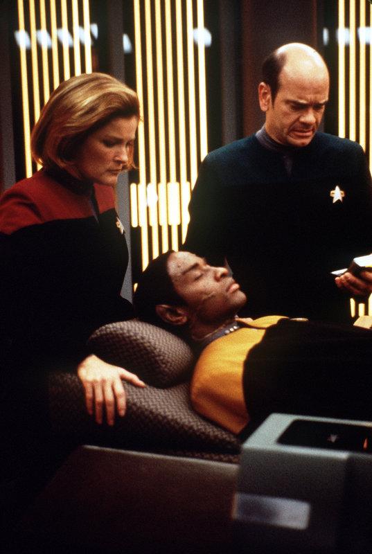 Der Doktor (Robert Picardo, r.) und Captain Janeway (Kate Mulgrew, l.) sind besorgt um Tuvok (Tim Russ, liegend), der nach einem Angriff fremder Wesen ins Koma gefallen ist. – Bild: Tele 5