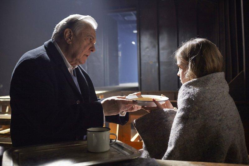 Dimitri (Valentin Platareanu) kümmert sich um seine kleine Geisel Sophie (Lena Meyer). – Bild: Guido Engels