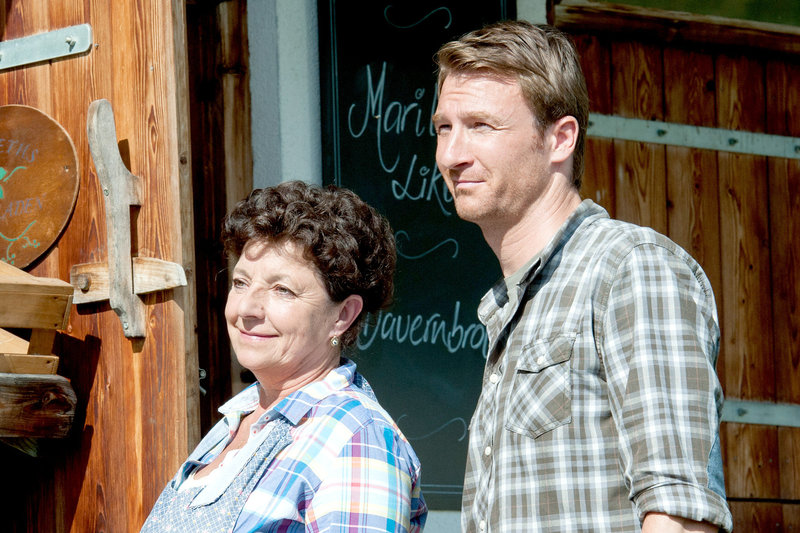 Lisbeth Gruber (Monika Baumgartner, l.) und Hans (Heiko Ruprecht, r.) freuen sich, dass auf ihrem Hof Mutter und Tochter wieder zueinanderfinden konnten. – Bild: SRF 1