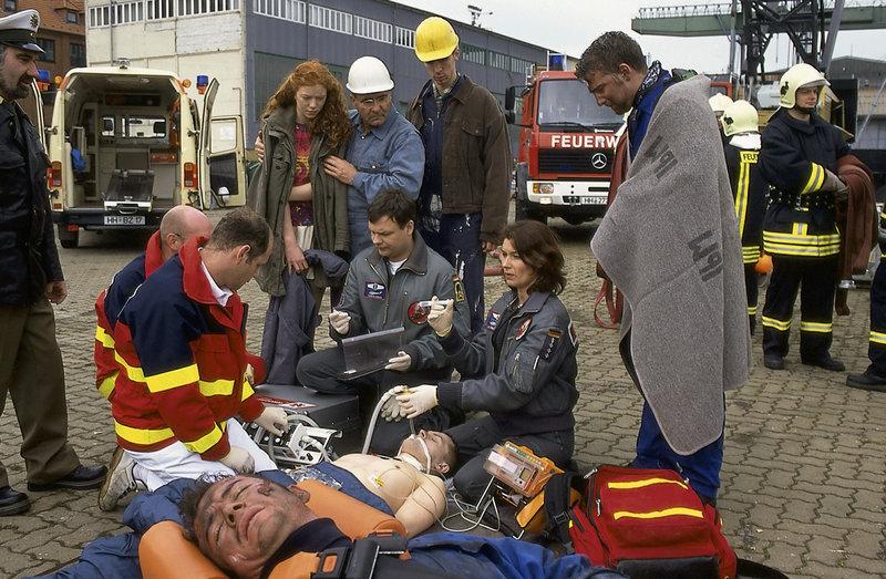 Thomas (Ulrich Bähnk, 3.v.r.) und Ilona (Julia Heinemann, 2.v.r.) kämpfen um das Leben der Verletzten, die bei einer schweren Verpuffung auf der Reparaturwerft verunglückt sind. – Bild: ZDF und Boris Laewen