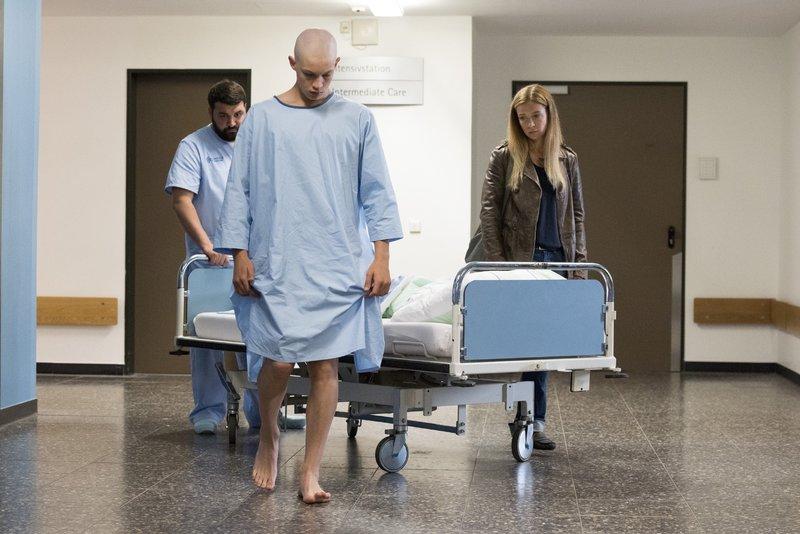 Jonas Till Neumann (Damian Hardung) will ein letztes Mal seine Beine spüren, bevor er operiert und ein Bein amputiert wird. Pfleger Dietz (Sahin Eryilmaz) und Mutter Anne Neumann (Alexandra Schalaudek) gewähren ihm den letzten Wunsch. – Bild: RTL Passion / Martin Rotte