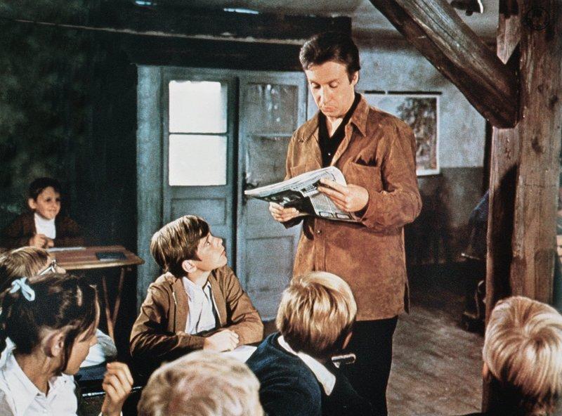 Peter Bach (Peter Alexander, stehend), zweifacher Doktor, ist versehentlich als Lehrer an der Zwergschule von Tuttelbach gelandet, fühlt sich aber mit seinem Neffen Jan (Heintje, 4. v. li.) sehr wohl dort. – Bild: MDR/ARD/Degeto