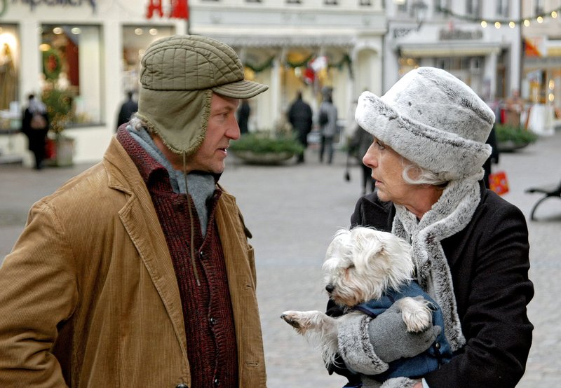 Elvira Hertzfeld (Rosemarie Fendel) will nicht, dass Straßenmusikant Paul (Miroslav Nemec) seinem Hund erlaubt, mit ihrer Hündin Minou anzubändeln. Auf viel Verständnis bei Paul stößt sie dabei nicht. Aber im übrigen ist der Mann überaschend höflich! – Bild: SWR/Schweigert