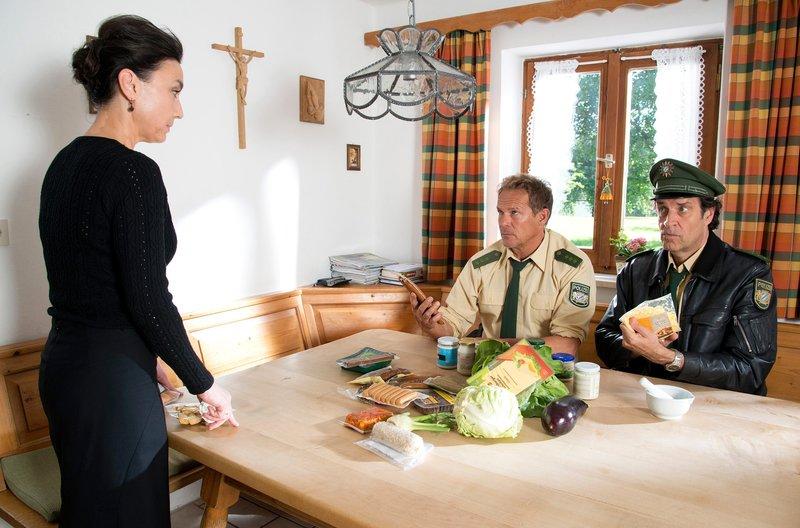 Hubert (Christian Tramitz, M.) und Staller (Helmfried von Lüttichau, r.) suchen bei Sabine Lange (Tatjana Clasing, l.), nach vergifteten Lebensmitteln. – Bild: ARD/TMG/Marco Meenen