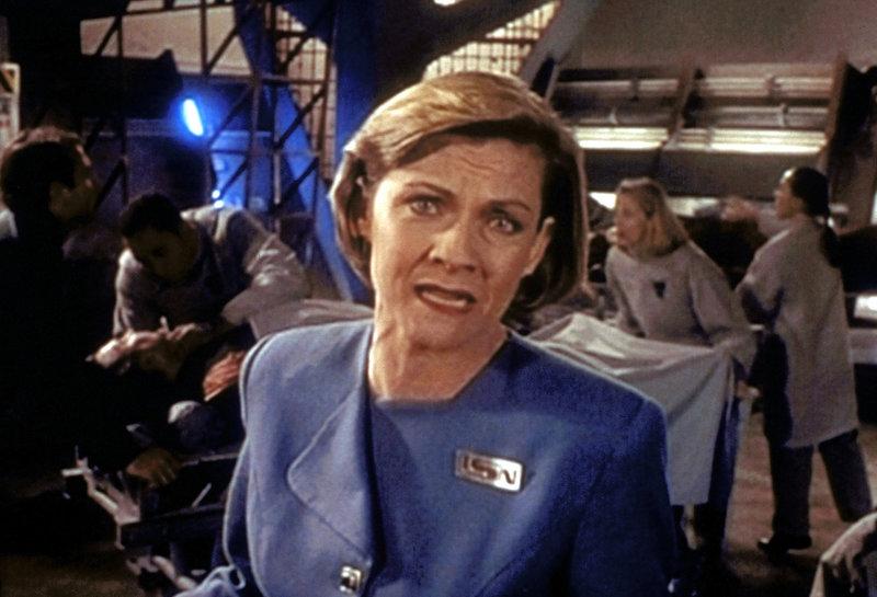 Unmittelbar nach dem Zusammenstoß zwischen Narn und Centauri informiert Cynthia Torqueman (Kim Zimmer) ihre Zuschauer über die Katastrophe. Im Hintergrund werden Verletzte behandelt. – Bild: ProSieben MAXX