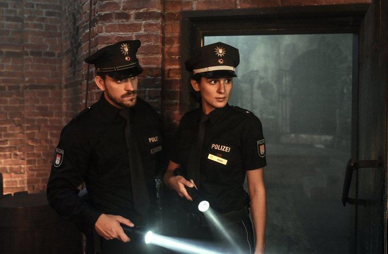 Kris (Marc Barthel, l.) und Pinar (Aybi Era, r.) sehen sich in dem Gruselkabinett um, in dem Helmut Ganser zusammengebrochen ist. – Bild: ZDF und Marion von der Mehden.