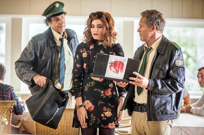 Agenturchefin Nina Schulz (Eva Bay, M.) verhält sich in den Augen von Hubert (Christian Tramitz, r.) und Staller (Helmfried von Lüttichaus, l.) sehr verdächtig. – Bild: ARD/BR/TMG/Chris Hirschhäuser