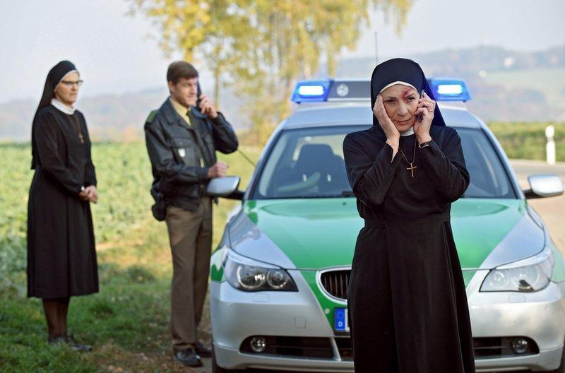 Schwester Hildegard (Andrea Sihler, l.) steht unter Schock, Mutter Oberin Theodora (Nina Hoger, r.) und Polizist Meier (Lars Weström, l.) rufen Verstärkung herbei. – Bild: ARD/Barbara Bauriedl