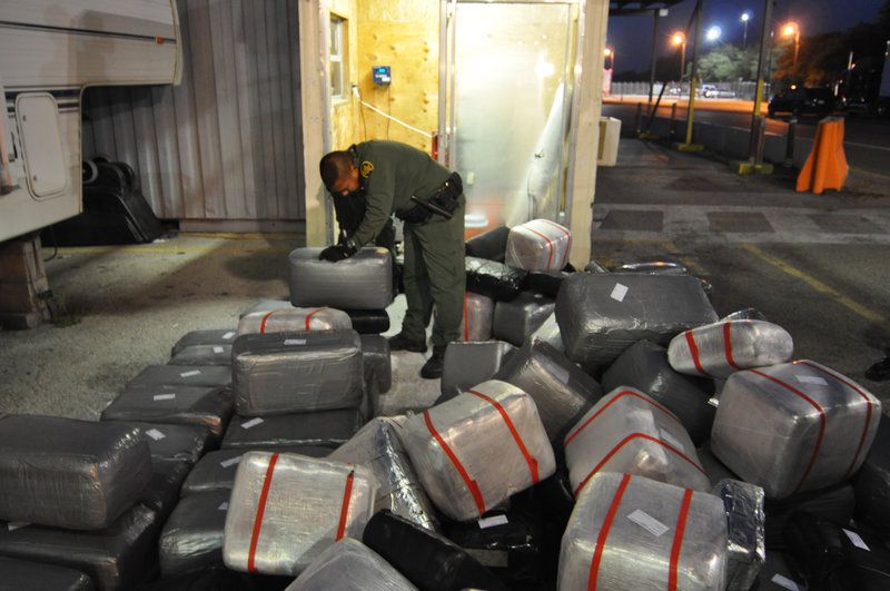 Falfurrias, Texas, USA: A Border Patrol agent organizes a pile of marijuana bundles discovered behind a false wall in a watermelon truck at Falfurrias checkpoint. (Photo Credit: NGT) – Bild: NGT