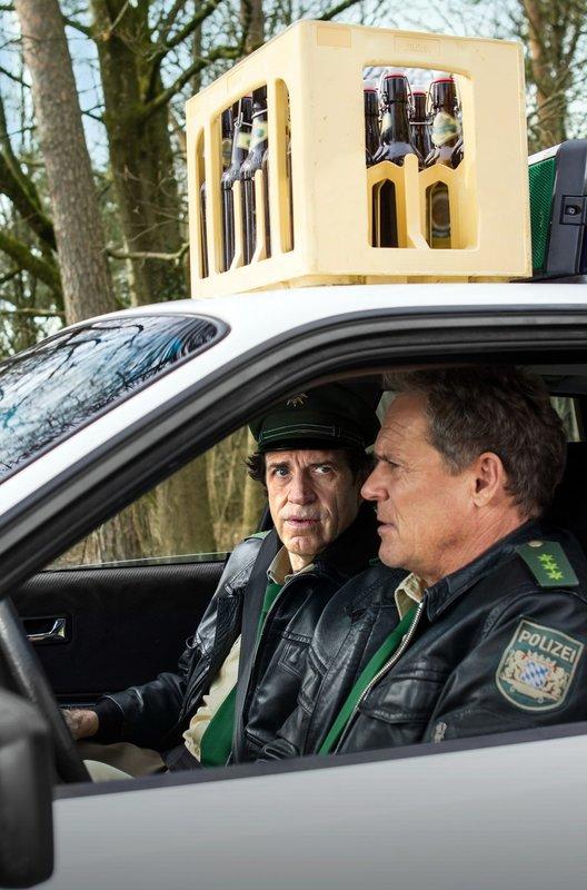 """Hubert (Christian Tramitz, rechts) und Staller (Helmfried von Lüttichau) haben ihr neues """"Accessoire"""" auf dem Dach des Polizeiautos noch nicht bemerkt. – Bild: ARD/BR/TMG/Chris Hirschhäuser"""