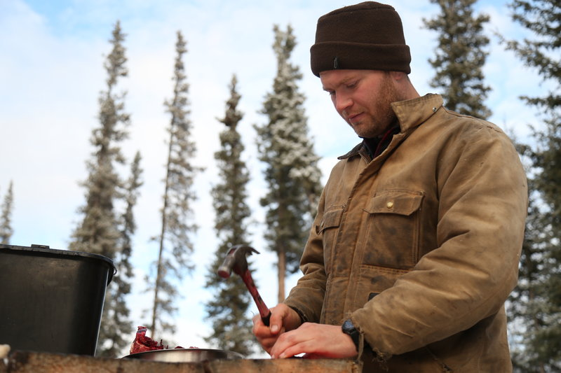 Tyler cutting meat at a table outside. – Bild: Animal Planet / Discovery Communications