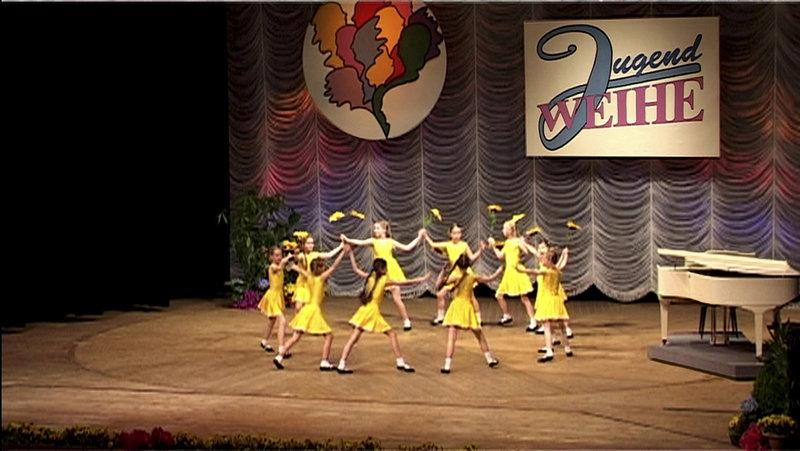 Totale der Bühne des HKB Neubrandenburg bei einer Jugendweiheveranstaltung. 10 kleine Mädchen in gelben Kleidchen und mit Sonnenblumen haben sich an den Händen gefasst und bilden einen Kreis. – Bild: ZDF und Wiltrud Baier