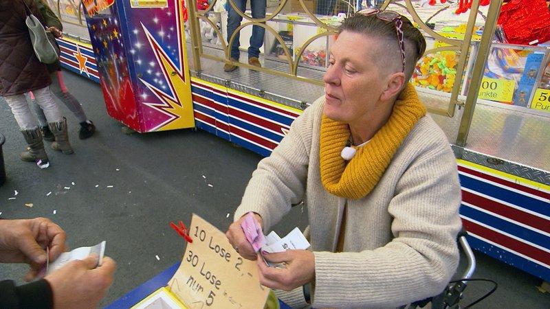 Anette ist Frührentnerin und leidet an schweren gesundheitlichen Problemen. Im Alltag ist die 59-Jährige auf einen Rollator angewiesen und kommt mit ihrer Rente kaum aus. Um zu überleben verkauft sie Lose auf dem Jahrmarkt.Anette ist FrĂĽhrentnerin und leidet an schweren gesundheitlichen Problemen. Im Alltag ist die 59-Jährige auf einen Rollator angewiesen und kommt mit ihrer Rente kaum aus. Um zu ĂĽberleben verkauft sie Lose auf dem Jahrmarkt. – Bild: RTL II