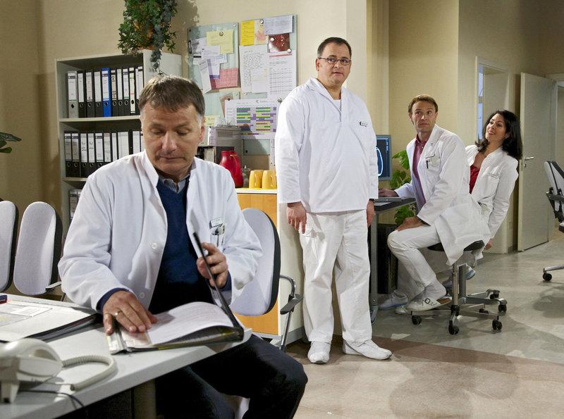 Hans Peter Brenner (Michael Trischan, 3. von rechts) hätte fast seinen Prüfungstermin für Nahttechniken verschwitzt. Nun steht er mächtig unter Druck, sucht dringend jemanden, der mit ihm die verschiedenen Techniken noch einmal durchgeht. Doch weder Dr. Elena Eichhorn (Cheryl Shepard, rechts) noch Dr. Martin Stein (Bernhard Bettermann) haben so kurzfristig Zeit, von Dr. Roland Heilmann (Thomas Rühmann, links) ganz zu schweigen. Elena rät Brenner Dr. Kaminski um Hilfe zu bitten. Hans-Peter findet diese Idee nahezu lächerlich - Kaminski wäre wohl der Letzte, der ihm helfen würde. – Bild: BR Fernsehen