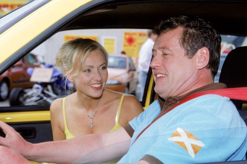 Stefanie (Dana Golombek) ist ganz begeistert von dem quietschgelben Kleinwagen und möchte ihn kaufen. Benno (Willi Thomczyk) soll sein Urteil als Fachmann dazu abgeben. – Bild: RTLplus