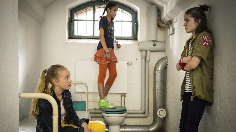 Kiara (Johanna Götting, links), Lisha (Emma Roth) und Mia (Marleen Quentin, rechts) gucken sich am Projekttag ein Gefängnis von innen an.– Bild: NDR/Boris Laewen