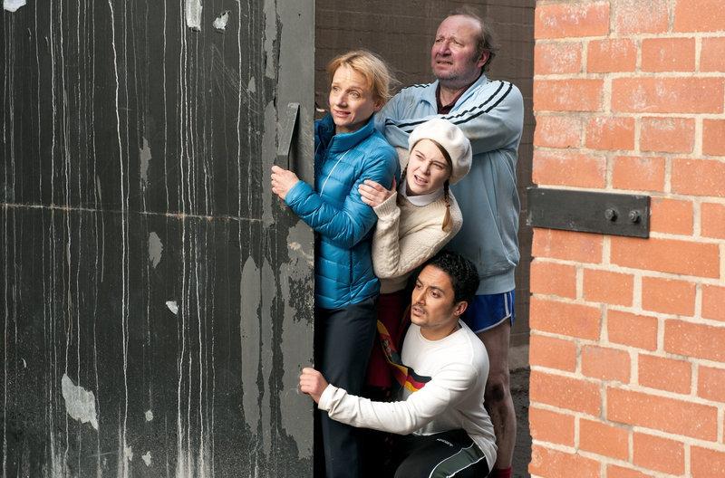 Da Titus auf eine Mine getreten ist, verstecken sich die anderen Mitarbeiter hinter dem Eingangstor des Sprach- und Kulturinstitutes. Von oben: Gmeiner (Rainer Reiners), Dr. Eckart (Christina Grosse), Jördis (Nadja Bobyleva) und Haschim (Omar El-Saeidi). – Bild: NDR/BR/WDR/Novafilm