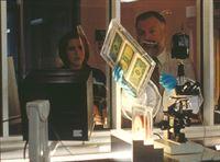 Scully (Gillian Anderson, l.) stellt mit Hilfe des Seuchen-Spezialisten Dr. Leavitt (John B. Lowe, r.) fest, dass die Dollar-Noten mit einem tödlichen Gift, das wahrscheinlich gentechnisch hergestellt worden ist, besprüht wurden. – © TM + © 2000 Twentieth Century Fox Film Corporation. All Rights Reserved. Lizenzbild frei