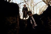 Mulder (David Duchovny, r.) und Scully (Gillian Anderson, l.) untersuchen ein Schlammloch, das angeblich gegraben wurde, um einen Mann darin versinken zu lassen. – © TM + © 2000 Twentieth Century Fox Film Corporation. All Rights Reserved. Lizenzbild frei