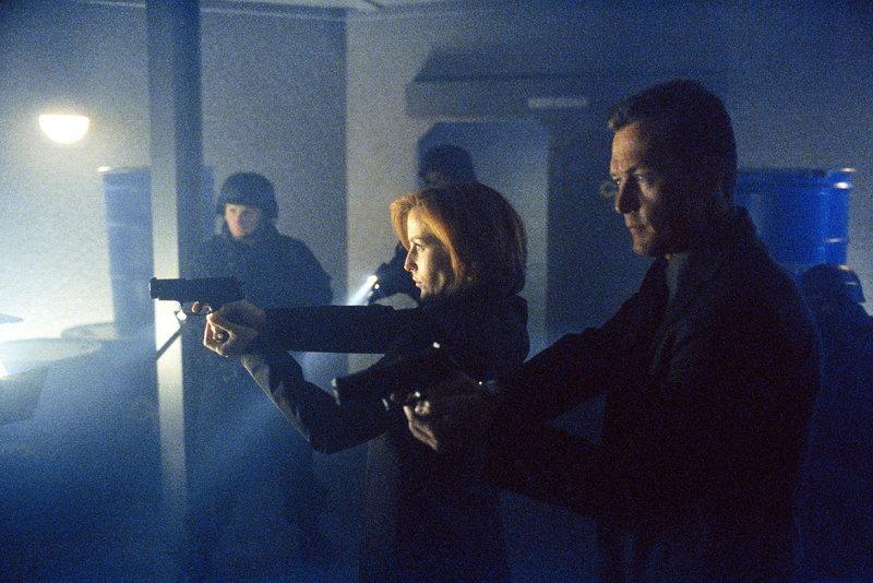 FBI-Agent Doggett (Robert Patrick, r.) und Scully (Gillian Anderson, M.) durchsuchen die Räume einer Kammerjägerfirma, die den Brüdern Randall und Dwight Cooper gehört. – Bild: ProSieben MAXX