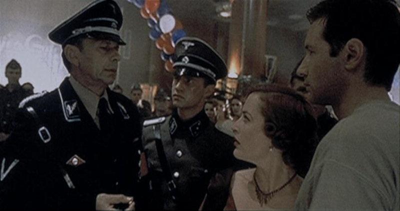 """Mulder (David Duchovny, r.) und Scully (Gillian Anderson, 2.v.r.) werden von dem Befehlshaber der Waffen-SS (William B. Davis, l.) auf der """"Queen Anne"""" festgehalten. – Bild: ProSieben MAXX"""