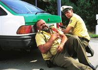 Polizist Herzberger (Dietmar Huhn, li.) wurde angeschossen. Polizist Bonrath (Gottfried Vollmer) kümmert sich um ihn. – © RTL Crime