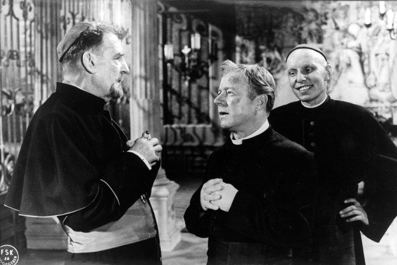 Der Bischof (Rudolf Forster, links) hat Pater Brown (Heinz Rühmann, Mitte) wieder einmal nach Dublin zitiert, um ihm gehörig den Kopf zu waschen. Er wünscht, daß ein für allemal Schluß ist mit der Detektiv-Spielerei! Koadjutor Malone (O. E. Fuhrmann) beobachtet die Situation mit gewisser Schadenfreude. – Bild: BR/ARD Degeto