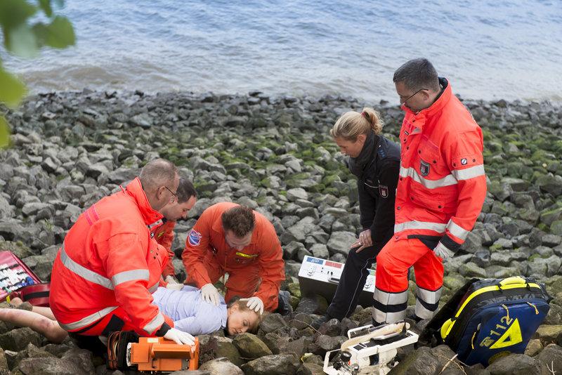Dr. Haase (Fabian Harloff, M.) versorgt die verletzte Frau (Carina Wiese, liegend), die am Elbufer gefunden wurde. Franzi (Rhea Harder, 2.v.r.) versucht herauszufinden, was passiert ist. – Bild: ZDF und Boris Laewen-bola
