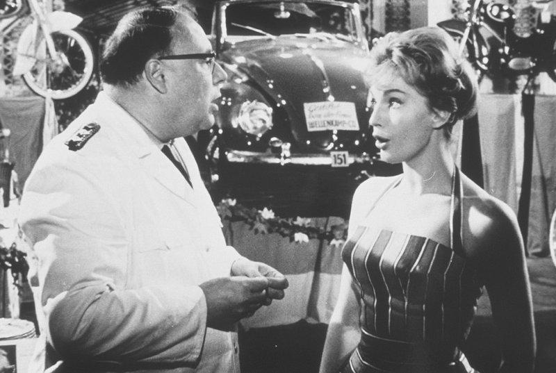 Karin (Maria Perschy) schiebt ihrem Vater Eberhard (Heinz Erhardt) das Gewinnlos der Polizeitombola zu: ein VW Cabriolet. – Bild: KIRCH MEDIA GMBH & CO KG AA