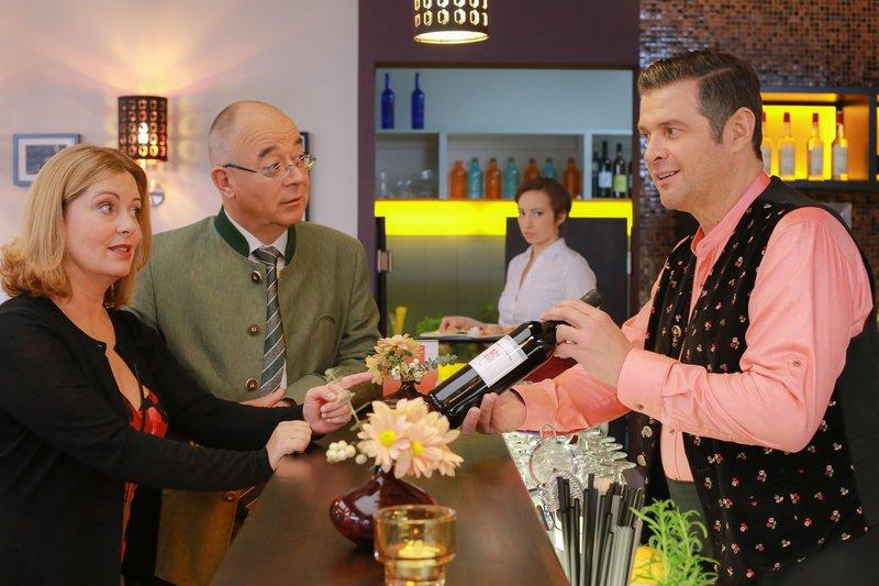 Jo (Christian K. Schaffer, r.) empfiehlt Marie (Karin Thaler, l.) und Herrn Achtziger (Alexander Duda, 2.v.l.) einen Wein als Präsent, was Mitarbeiterin Steffi (Regina Speiseder, 2.v.r.) skeptisch beobachtet. – Bild: ZDF und Christian A. Rieger - klick.
